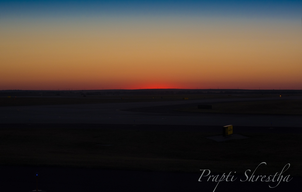 Sunset seen from the plane window at Denver International Airport during sunrise