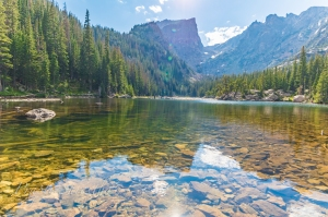 Dream Lake at Rocky Mountain National Park capturing the reflection of Hallett Peak and trees, rocks visible under the clear water of the lake