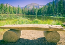 Bench in front of Nymph Lake at Rocky Mountain National Park on a sunny day with Longs Peak behind the lake