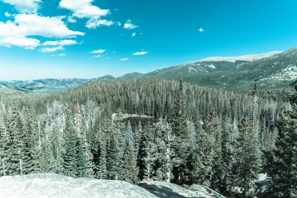 View of Rocky Mountain National Park with Nymph Lake below, surrounded by alpine trees, blue sky and cloud covering